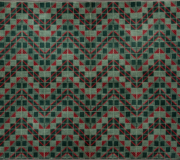 Geometric chevron design in red and two shades of green, consisting of a grid of squares with diagonal lines